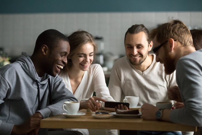 Millennial girl showing funny photos or videos on cellphone to multiracial young friends at cafe meeting, diverse happy friends laughing using mobile phone app together sitting at coffee house table